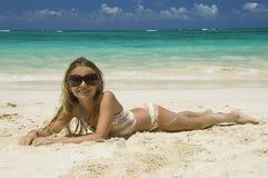 Junges Mädchen, das auf weißem sandigem Strand niederlegt. Stockbilder