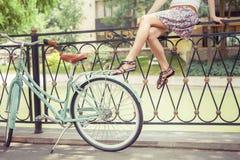 Junges Mädchen, das auf Zaun nahe Weinlesefahrrad am Park sitzt Lizenzfreie Stockbilder