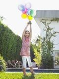 Junges Mädchen, das Ballone im Rasen hält Lizenzfreie Stockfotografie