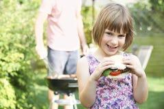 Junges Mädchen, das Beefburger am Familien-Grill isst Stockbild