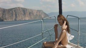 Junges Mädchen, das Bild von ihrer Freundin auf der Yacht macht lizenzfreie stockfotografie