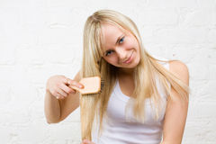 Junges Mädchen, das blondes Haar kämmt Stockfoto