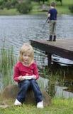 Junges Mädchen, das Computerspiel in der Natur spielt Stockfoto