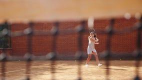 Junges Mädchen, das den Ball mit dem Tennisschläger während des Trainings blockiert stock video footage