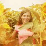 Junges Mädchen, das den Geruch von Blumen auf der gelben Feld Erholung, Sommer, Natur, Ferienkonzept genießt stockbild