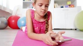 Junges Mädchen, das den Smartphone liegt auf dem Boden verwendet stock video footage