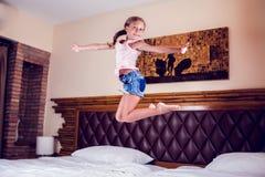 Junges Mädchen, das den Spaß springt auf Bett im Schlafzimmer hat stockfoto