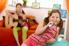 Junges Mädchen, das in der Hand mit Mikrofon lächelt Lizenzfreies Stockfoto