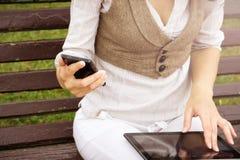 Junges Mädchen, das draußen auf einer Bank mit ihrer Tablette und Handy in den Händen sitzt Stockfotos