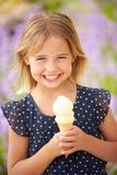 Junges Mädchen, das draußen Eiscreme isst Stockfotografie