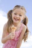 Junges Mädchen, das draußen Eiscremekegel isst Stockfoto