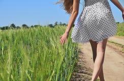Junges Mädchen, das draußen Natur genießt Schönes jugendliches vorbildliches Mädchen im gelben Kleid gehend auf das Weizenfeld im Stockfoto