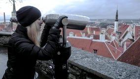 Junges Mädchen, das durch binokulares schaut stockfoto