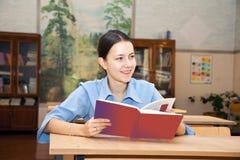 Junges Mädchen, das ein Buch in der Bibliothek liest Stockfoto