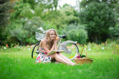Junges Mädchen, das ein Buch in der Landschaft liest Stockbild