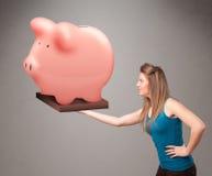 Junges Mädchen, das ein enormes Spareinlagensparschwein hält Lizenzfreie Stockfotos