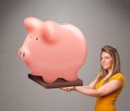 Junges Mädchen, das ein enormes Spareinlagensparschwein hält Lizenzfreie Stockbilder