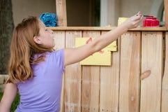 Junges Mädchen, das ein Limonadestandzeichen malt Stockfotografie