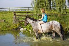 Junges Mädchen, das ein Pferd reitet lizenzfreie stockfotografie