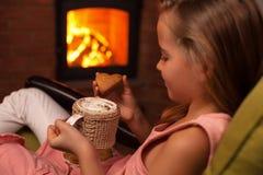Junges Mädchen, das ein Plätzchen mit einer heißen Schokolade sitzt durch genießt stockfotografie