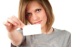 Junges Mädchen, das ein Schild auf Weiß anhält stockbild