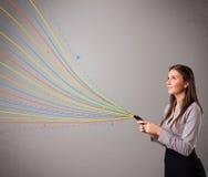 Junges Mädchen, das ein Telefon mit bunten abstrakten Linien hält Lizenzfreie Stockfotografie