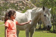 Junges Mädchen, das ein wildes Pferd berührt lizenzfreies stockbild