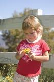 Junges Mädchen, das eine Blume anhält Stockfoto