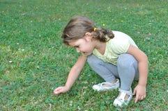 Junges Mädchen, das eine Blume auswählt Stockfotos
