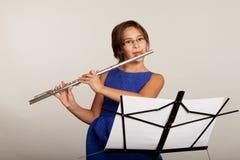 Junges Mädchen, das eine Flöte spielt Stockfoto