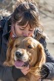 Junges Mädchen, das eine Hundegolden retriever-Zucht küsst Liebe stockbild