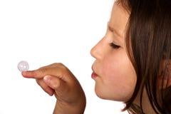 Junges Mädchen, das eine Luftblase weg von ihrem Finger durchbrennt Stockfoto