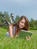 Junges Mädchen, das eine Tablette im Park verwendet Lizenzfreie Stockfotografie