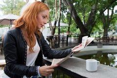 Junges Mädchen, das eine Zeitung in der Cafeteria liest Stockfotografie
