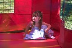 Junges Mädchen, das in einem aufblasbaren federnd sitzt Stockbild