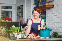 Junges Mädchen, das in einem Blumenladen arbeitet Stockfotos