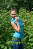 Junges Mädchen, das in einem Garten in den Büschen von Himbeeren steht Lizenzfreie Stockbilder