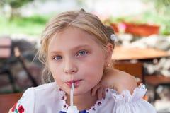 Junges Mädchen, das in einem im Freienkaffee aufwirft Lizenzfreie Stockfotos