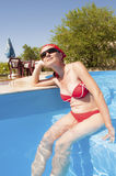 Junges Mädchen, das in einem Pool sitzt Lizenzfreie Stockfotografie