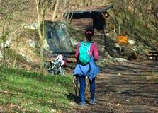 Junges Mädchen, das in einem Wald mit einer Buggy im Hintergrund wandert lizenzfreie stockfotos