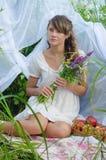 Junges Mädchen, das einen Blumenstrauß von Blumen hält Lizenzfreie Stockfotos