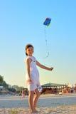 Junges Mädchen, das einen Drachen auf dem Strand fliegt Lizenzfreies Stockfoto