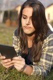 Junges Mädchen, das einen Ebuch Leser in einer Wiese liest lizenzfreies stockbild