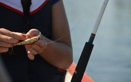 Junges Mädchen, das einen Fischereiköder behandelt Stockbilder