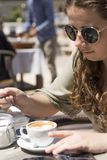 Junges Mädchen, das einen Kaffee an einem sonnigen Frühlingstag trinkt stockbilder