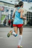 Junges Mädchen, das einen Marathon laufen lässt Stockbild