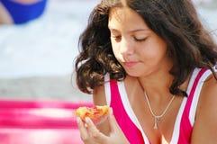 Junges Mädchen, das einen Pfirsich isst Stockbild