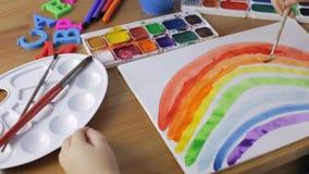 Junges Mädchen, das einen Regenbogen malt Aquarellmalereikonzept stock footage