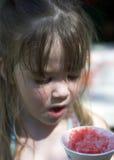 Junges Mädchen, das einen Schnekegel isst Stockfotos