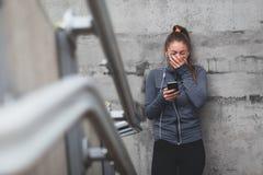 Junges Mädchen, das einen Smartphone lacht und hält Stockfotografie